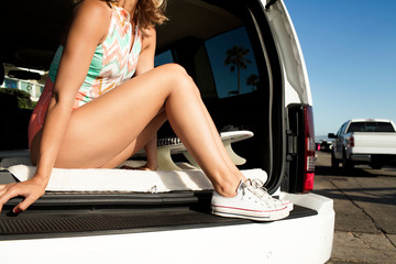 Young woman sitting in open trunk of car