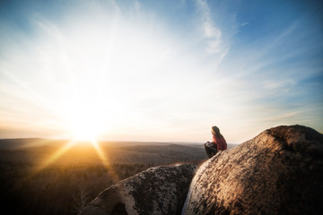 Young woman sitting on boulder