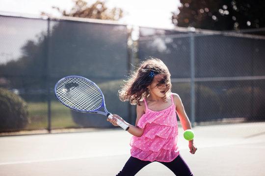 Girl (6-7) playing tennis