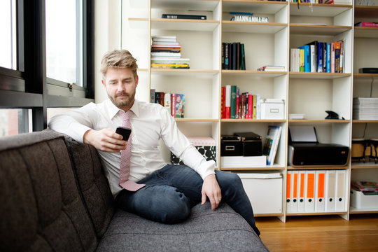 Businessman sitting on sofa using cell phone