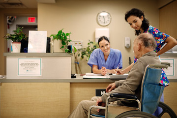 Doctor and female nurse talking to patient at reception desk