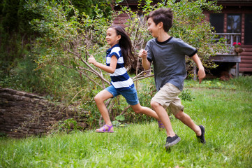 Kids (6-7, 8-9) running on grass Photo