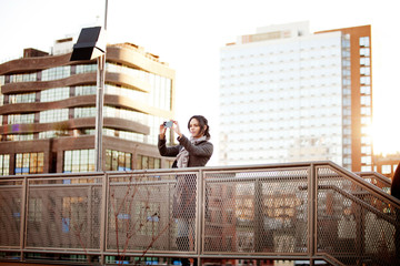 Young woman on foot bridge taking pictures