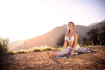 Young woman doing splits outside
