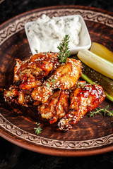 Fried glazed chicken wings in soy sauce and sesame. Cheese white sousa. Marinated vegetables on a ceramic plate. Background image. copy space