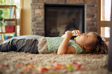 Little girl lying on carpet in living room