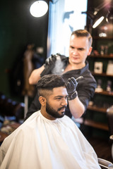 Barber combs his hair to a young guy with a beard and mustache and sprinkles hair on the spray gun. Barber Shop.