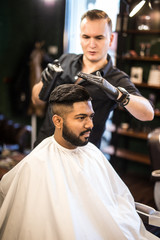 Barber splashes of spray on the client's hair. Haircut in the salon