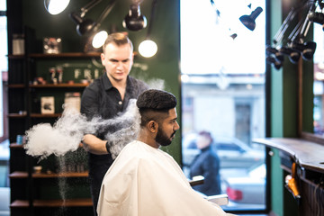 Bearded man with long beard, brutal, indian hipster with moustache, with stylish hair, haircut, getting powder on skin with makeup brush by barber or hairdresser hands at barbershop