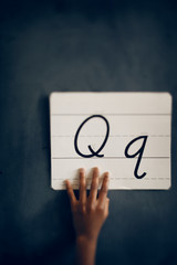 Human hand holding paper with letter Q