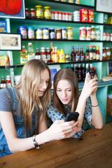 Girlfriends text messaging inside store