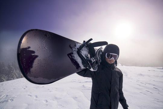Portrait of man carrying on shoulder snowboard