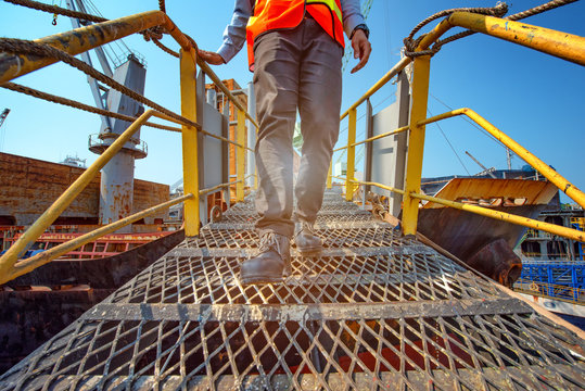 legs of worker or engineering wearing Safety shoes walking in mind step on the steel gangway bridge cross over at workplace, working in high stage and high level of insurance.