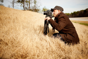Man photographing in field by road