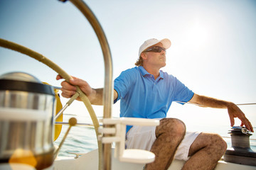 Man wearing eyeglasses steering yacht against clear sky