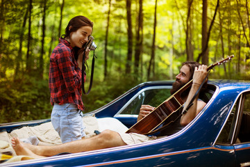 Young woman making picture of man playing guitar on back of pick-up truck