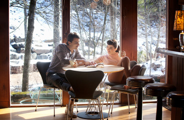 Couple reading and drinking at kitchen table