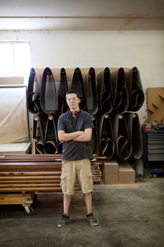 Portrait of young carpenter standing in woodshop