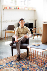 Portrait of mid adult man sitting in armchair in loft