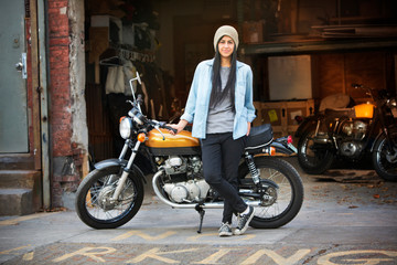 Young woman next to motorcycle