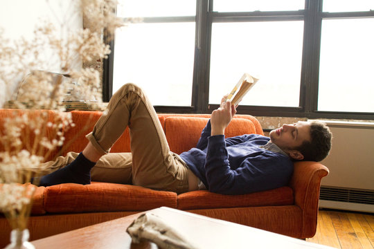 Young man relaxing on couch and reading book