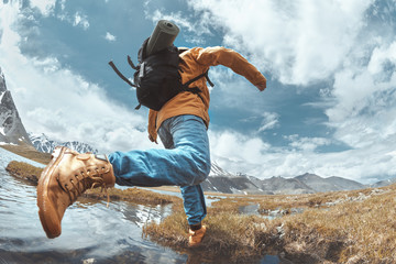 Man hiker jumps across water in mountain area Wall mural
