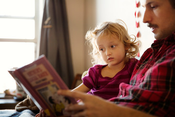 Small girl (2-3) reading book with father