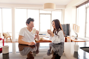 Couple drinking coffee at kitchen counter