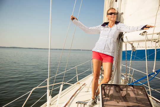 Woman leaning on helm of yacht