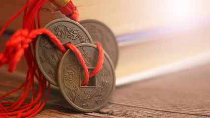 Three Chinese coins and books background