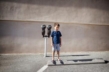 Boy (4-5) standing next to parking meter