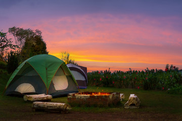 Camping tent of tourist with firepit beautiful sky in evening, Selective focus, Low light environment.