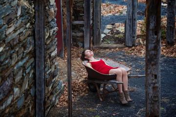 Young woman wearing red dress lying in push cart