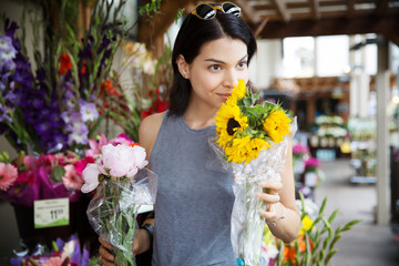 Young woman smelling sunflowers at flower market