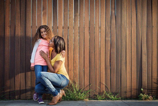 Portrait of mother and daughter in front of wooden wall