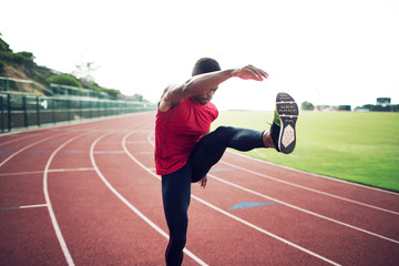 Sportsman standing on running track and stretching
