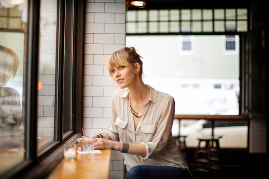 Young woman daydreaming by window in bar