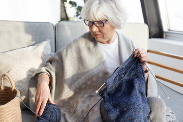 Indoor shot of serious concentrated elderly woman with gray hair sitting on couch in living room wearing glasses, knitting warm winter clothes for her internet website, selling homemade goods online