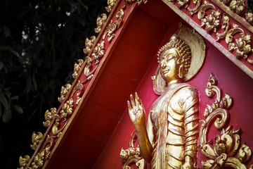 Great Gold Buddha statue with red background wall.