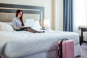 Successful female lawyer is resting at the hotel during business trip. Red-haired woman is lying on wide bed with a laptop, being elegantly dressed up, leaving her sexy pin-up heels on bed