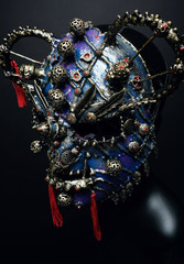 Iron demon mask with precious stones on dark background