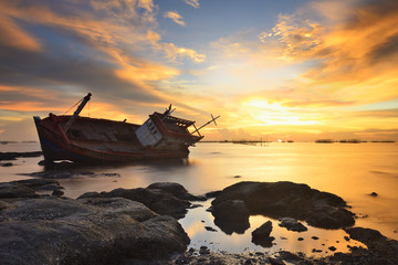 Wall Murals Shipwreck boat on the beach at sunset