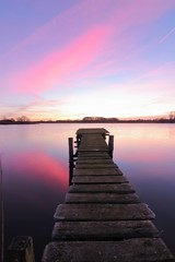 lakeside view with wooden jetty and pastel sky