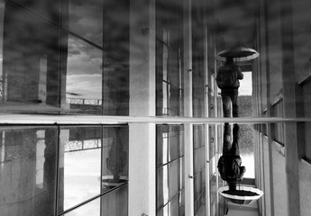 Street Photography - black and white reflection of a man with an umbrella.