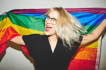 A beautiful blonde young woman with glasses holds a rainbow LGBTK flag and is having fun. Lesbian, gay, bisexual, transgender, queer. Homosexual man