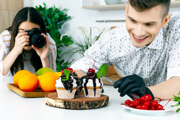 Stock photography backstage. Food stylist blogger prepare decorate vegan vegetarian healthy diet sugar lactose free cupcake cake with cherry, chocolate and fresh mint. Video photo blog vlog concept.