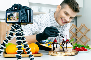 Cook chef food stylist men in black gloves prepare decorate paint vegan vegetarian healthy diet sugar lactose free cupcake cake with cherry and fresh mint on home kitchen. Food blogger make video vlog