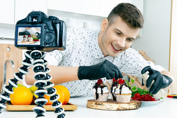 Cook chef food stylist men in black gloves prepare decorate splash vegan vegetarian healthy diet sugar lactose free cupcake cake with cherry and fresh mint on home kitchen Food blogger make video vlog