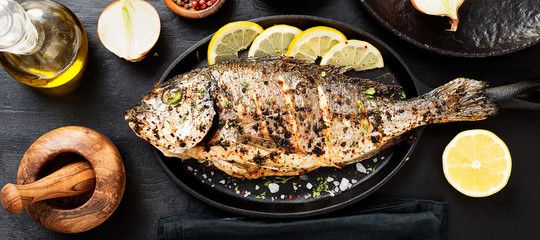 Tasty grilled fish dorado with  lemon on kitchen table. Wall mural
