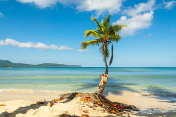 Woman in bikini relaxing on coconut palm tree on tropical beach with turquoise sea and blue sky in Las Galeras - Dominican Republic